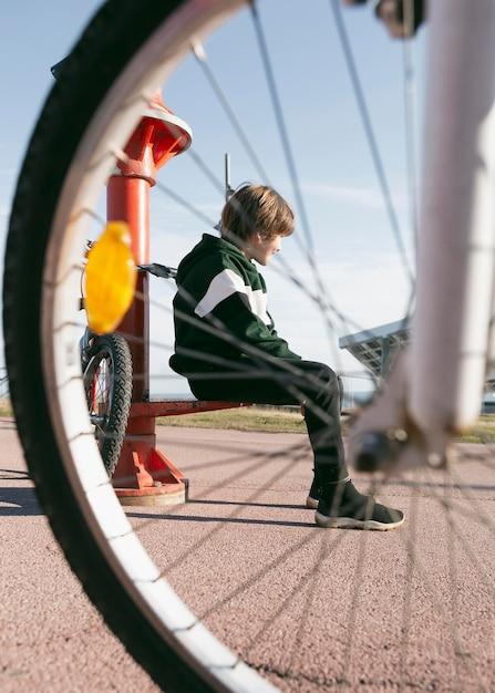 그의 자전거와 함께 야외에서 망원경 옆에 앉아 소년 무료 사진
