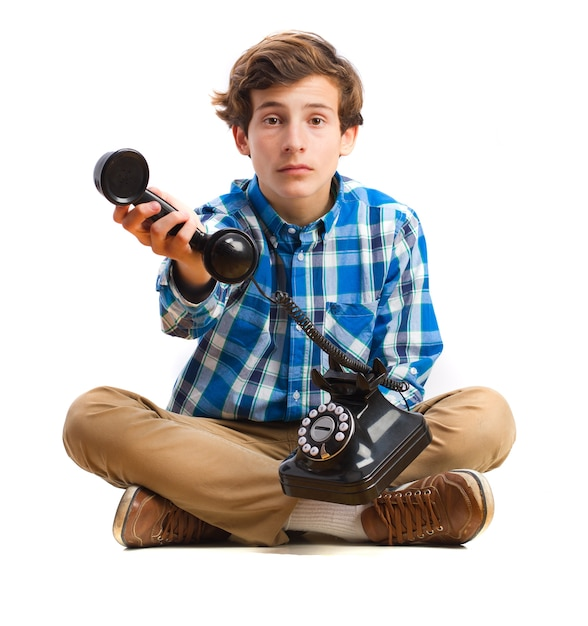 Boy sitting on the floor and holding a vintage telephone Free Photo