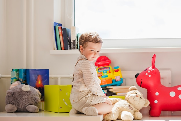 Boy sitting with toys at window Free Photo
