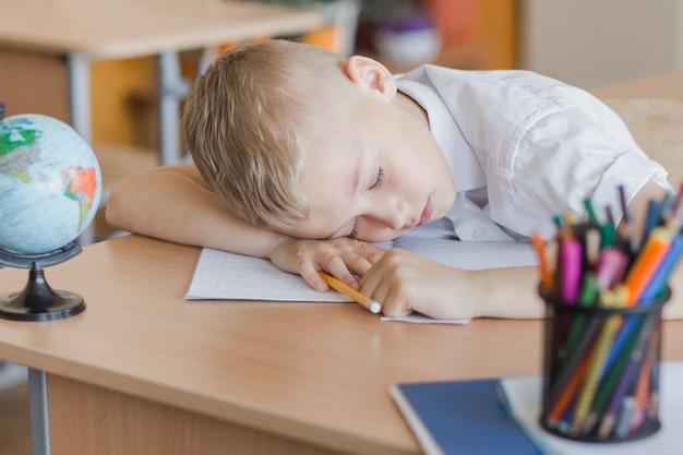 Boy sleeping on desk in classroom Free Photo