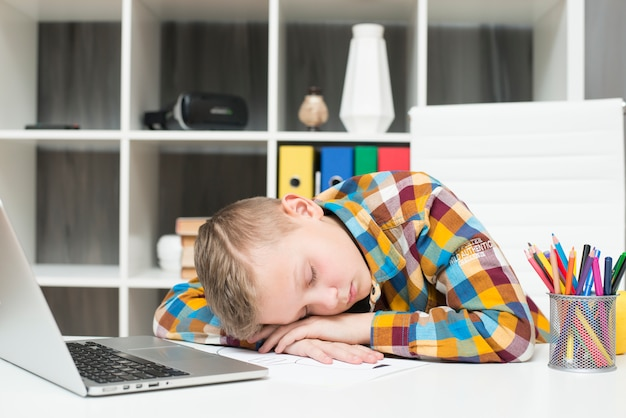 Boy sleeping in front of laptop on desk Free Photo