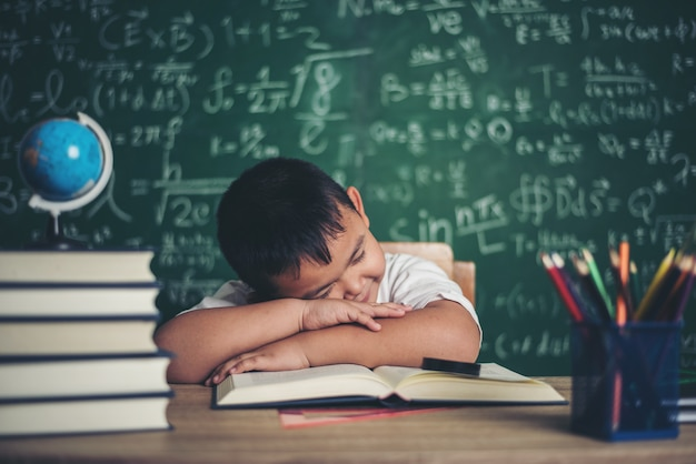 Boy sleeping on the books in the classroom. Free Photo