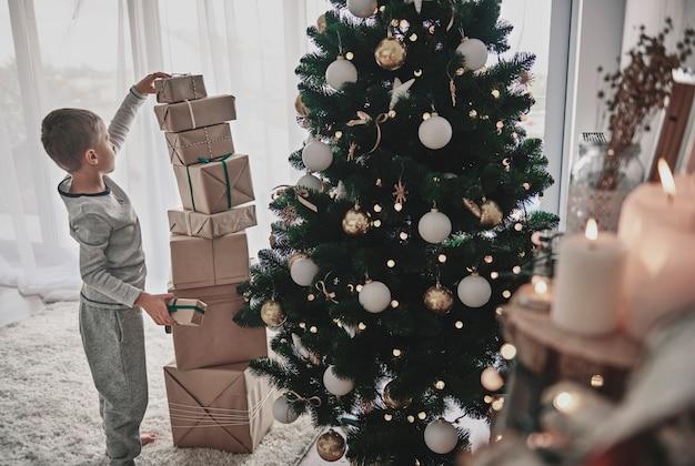 크리스마스 트리 옆에있는 소년 스태킹 크리스마스 선물 무료 사진