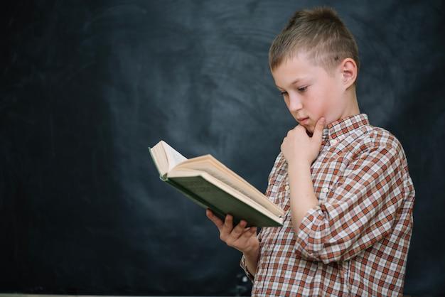Boy standing against blackboard reading book Free Photo