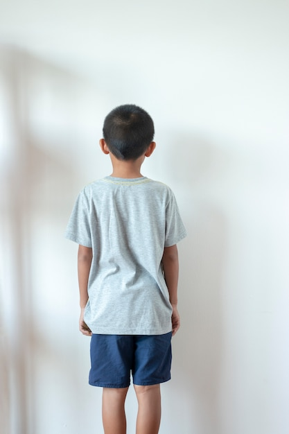 Boy standing in front of the wall in the corner of the roombecause of being punished by parents. Premium Photo