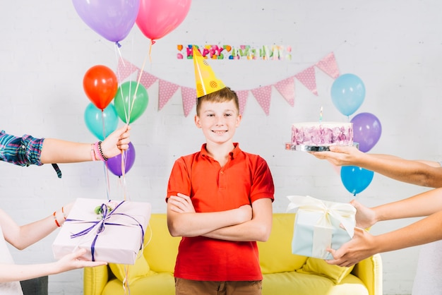 Boy standing between his friend's hand holding birthday cake; gifts and balloons Free Photo