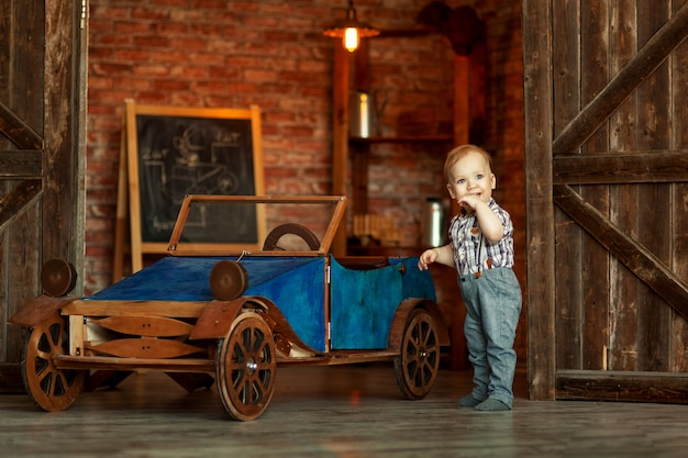 Boy standing at the mechanic with tools retro car near the garage Premium Photo