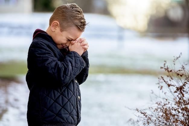 Ragazzo in piedi con gli occhi chiusi e pregando Foto Gratuite