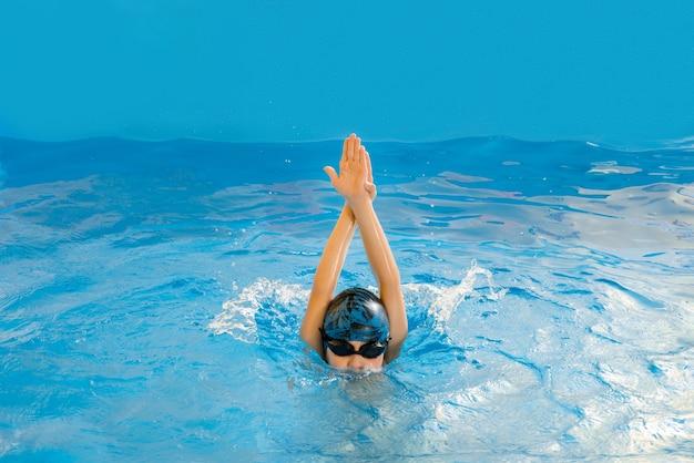 Мальчик плавает в крытом бассейне, развлекаясь во время урока плавания Premium Фотографии