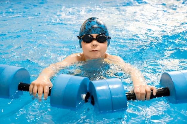 Мальчик плавает с водными гантелями в руках в бассейне Premium Фотографии