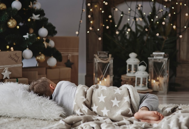 クリスマスツリーの横で昼寝をしている少年 無料写真