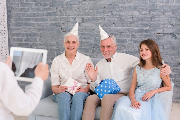 Boy taking photograph of his grandparents and sister sitting on sofa with digital tablet Free Photo