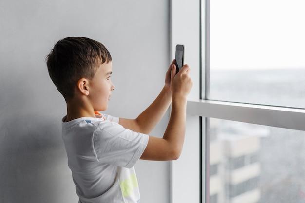 携帯電話で写真を撮る少年 無料写真