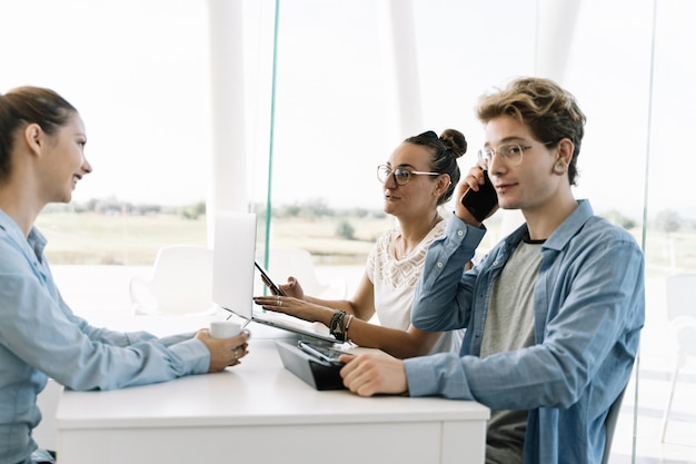 Boy talking to a mobile phone at a work table with other people in a coworking Premium Photo