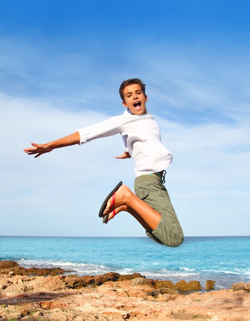 Boy teenager high fly jump on beach blue sky Premium Photo