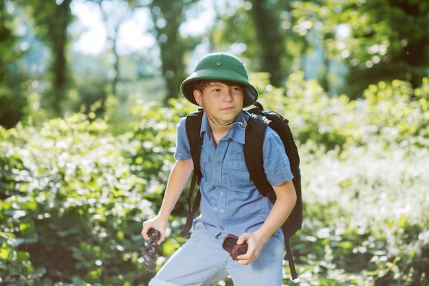 Мальчик-путешественник в шлеме играет в парке. Premium Фотографии