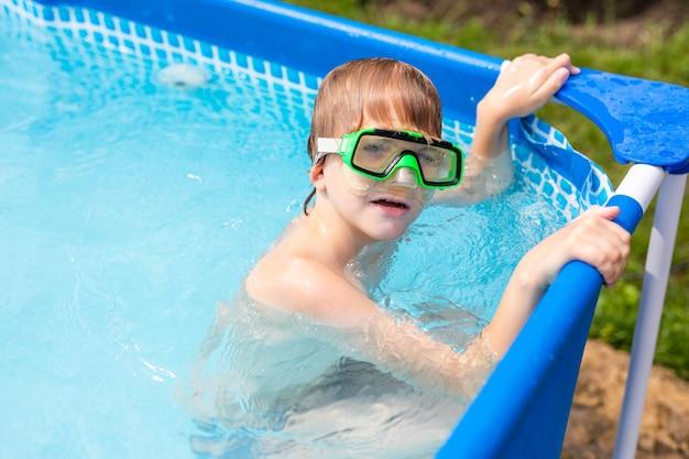 Мальчик под водой в маске. ребенок плавает в бассейне. мальчик в стаканах с водой в воде. Premium Фотографии
