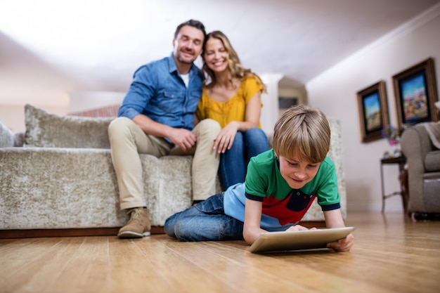 Boy using a digital tablet while parents sitting on sofa Premium Photo