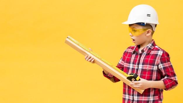 Boy using measuring tape copy space Free Photo