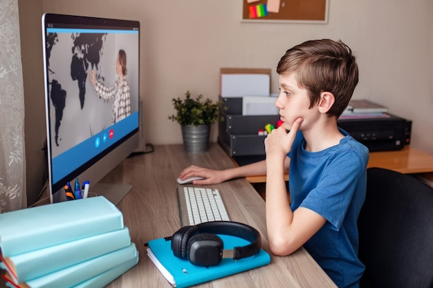 Boy video conferences with a tutor on the computer at home of distance learning Premium Photo