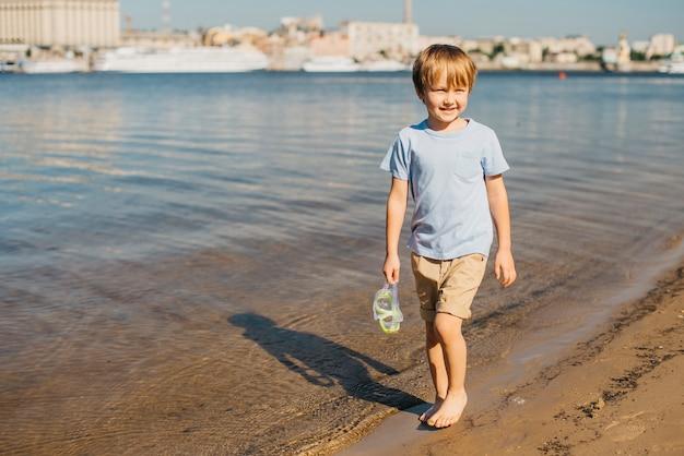 Boy walking along shore Free Photo
