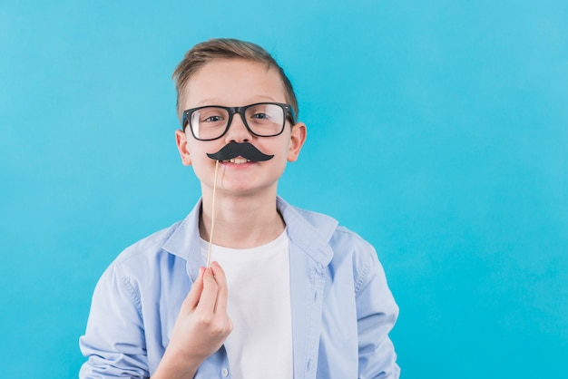 A boy wearing black eyeglasses holding black moustache prop in front of his upper lips Free Photo