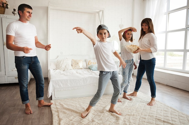 Boy wearing cap and dancing in front of his parents and sister at home Free Photo