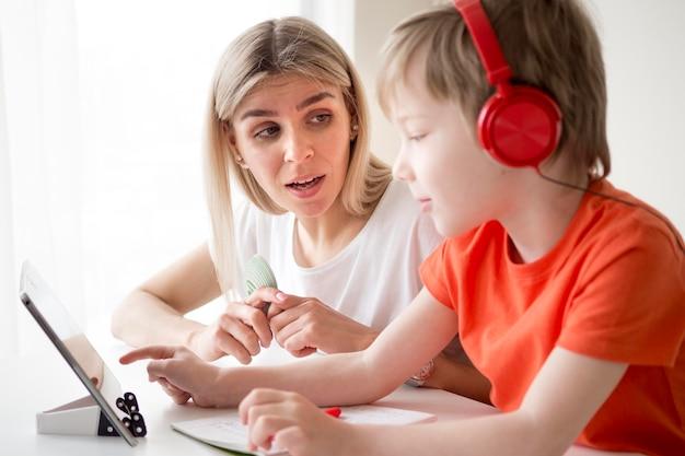 ヘッドフォンをつけて母親の隣に書いている少年 無料写真
