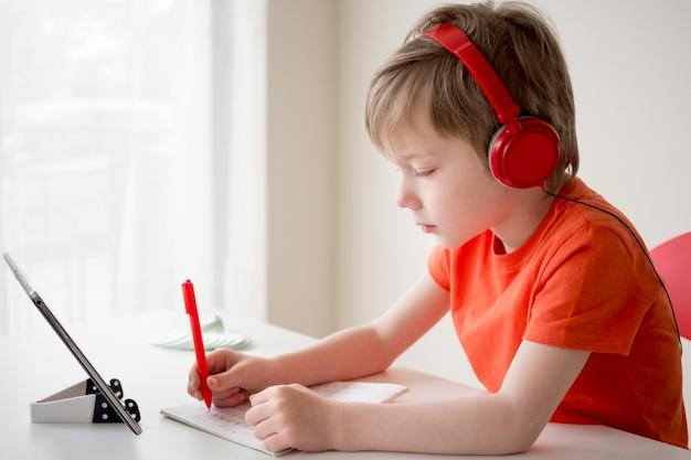 ヘッドフォンをつけて書いている少年 無料写真