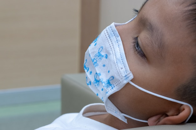 A boy wearing mask for protect disease because he get infection Premium Photo