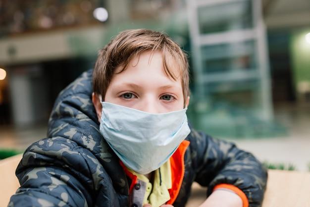 Мальчик в медицинской маске, задумчиво смотрящий, меры защиты от распространения covid-19 Premium Фотографии