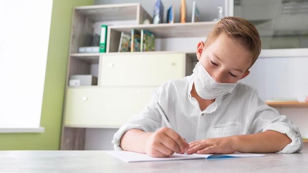 Ragazzo che indossa una maschera medica in classe con copia spazio Foto Gratuite
