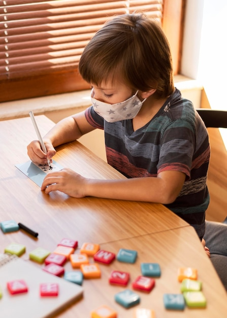Boy wearing medical mask at his online classes Free Photo
