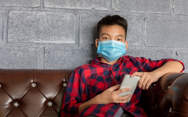 Boy wearing a protective face mask and holding a smartphone Premium Photo