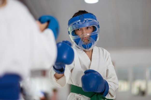 Boy wearing protective helmet and gloves boxing with friend Premium Photo