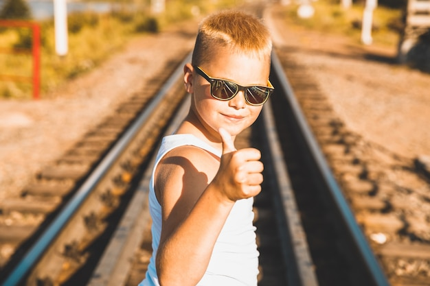 A boy in a white t-shirt and black glasses stands on the railway. Premium Photo