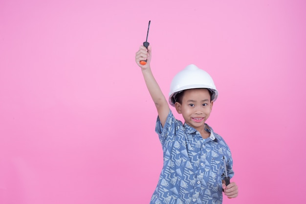 A boy who made a gesture from his hands wearing a helmet on a pink background. Free Photo
