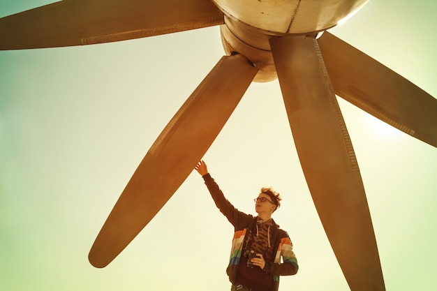 Boy with camera touches huge aircraft propeller Premium Photo