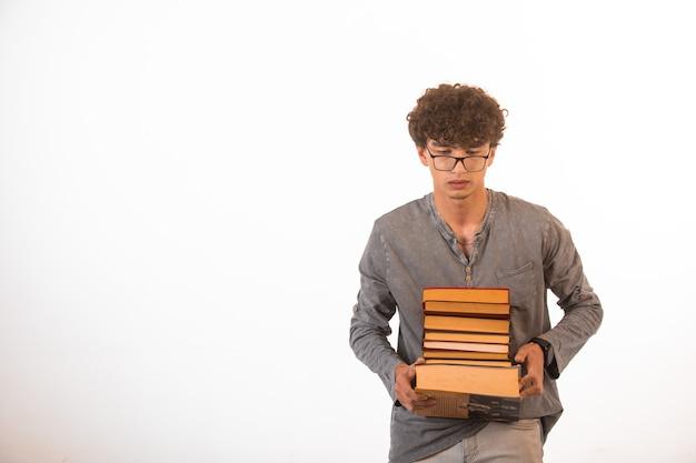 Ragazzo con i capelli ricci che indossa occhiali optique che trasportano una pila di libri. Foto Gratuite
