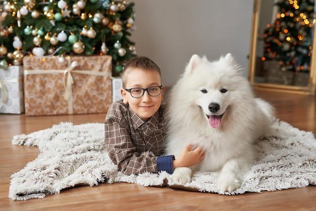 Boy with dog near christmas tree on christmas scene Premium Photo