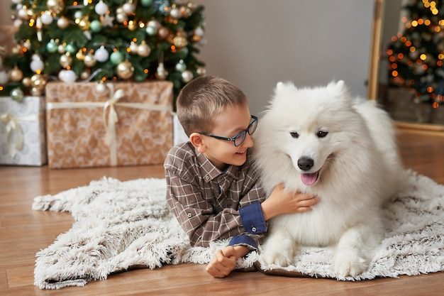 Boy with dog near christmas tree in christmas Premium Photo