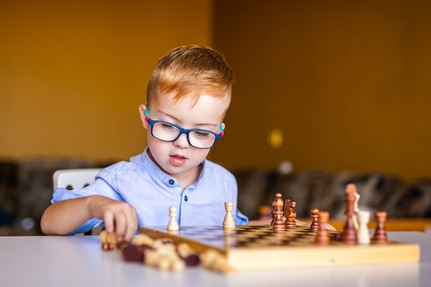 Boy with down syndrome with big glasses playing chess. Premium Photo