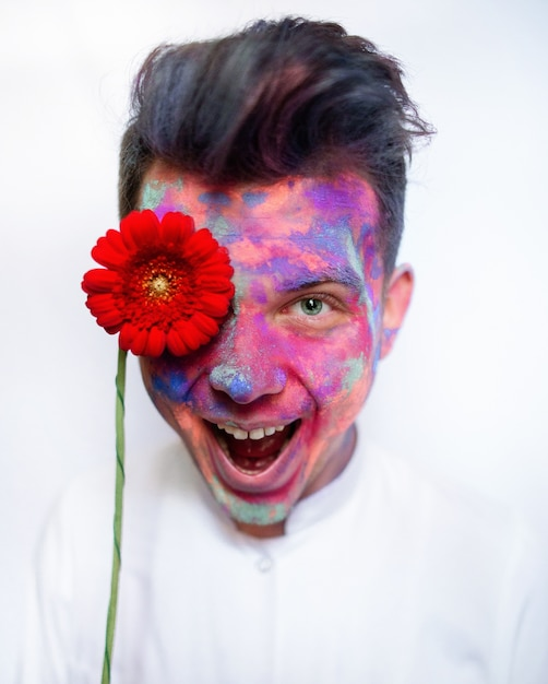 Boy with face covered with paints holds red flower before his eye Premium Photo