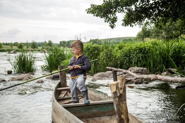 Мальчик с удочкой в деревянной лодке Premium Фотографии