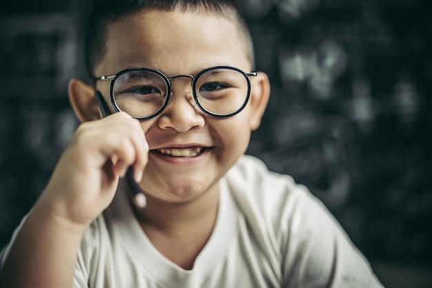 Un ragazzo con gli occhiali seduto in classe a studiare Foto Gratuite