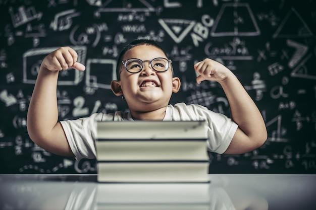 Un ragazzo con gli occhiali seduto nello studio e con entrambe le braccia perpendicolari Foto Gratuite