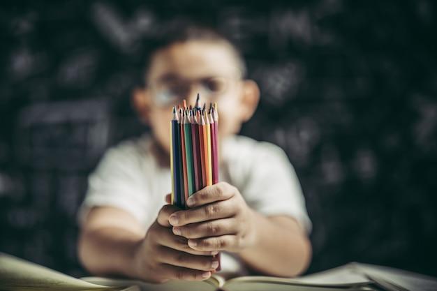 Un ragazzo con gli occhiali seduto con molte matite colorate Foto Gratuite
