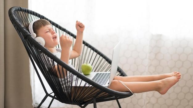 Ragazzo con le cuffie e computer portatile sulla sedia Foto Gratuite