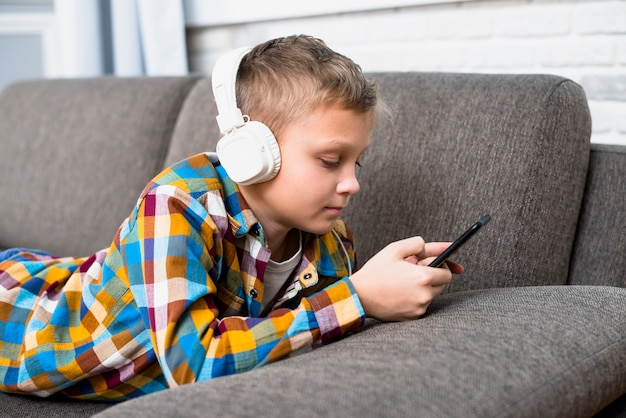 Boy with headphones using smartphone Free Photo