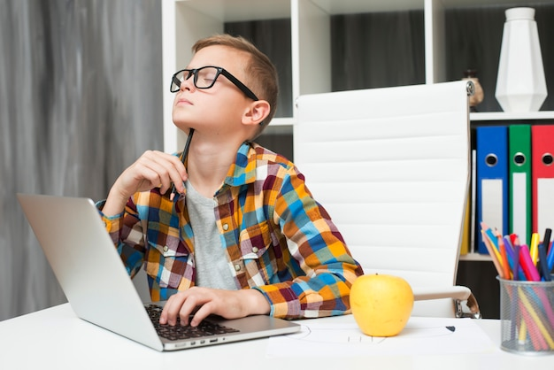 Boy with laptop at desk Free Photo